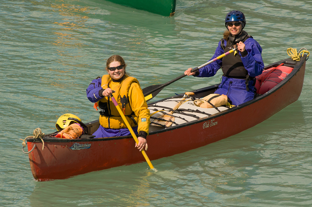 Two women paddle a red canoe on the Kenai River system in Alaska.
