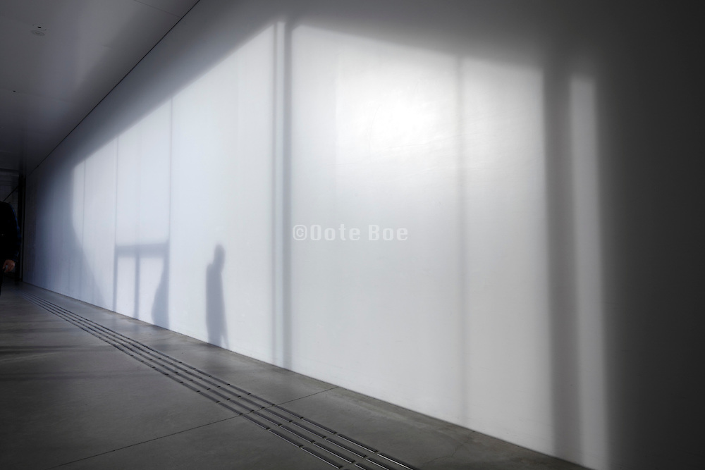 silhouette of person and large glass window projected on wall in corridor