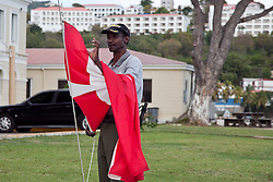 Officer James Francis changes over the Dutch Flag to the American Flag in commemoration of Transfer Day, the day in 1917 when the islands were transferred from Denmark to the United States of America.