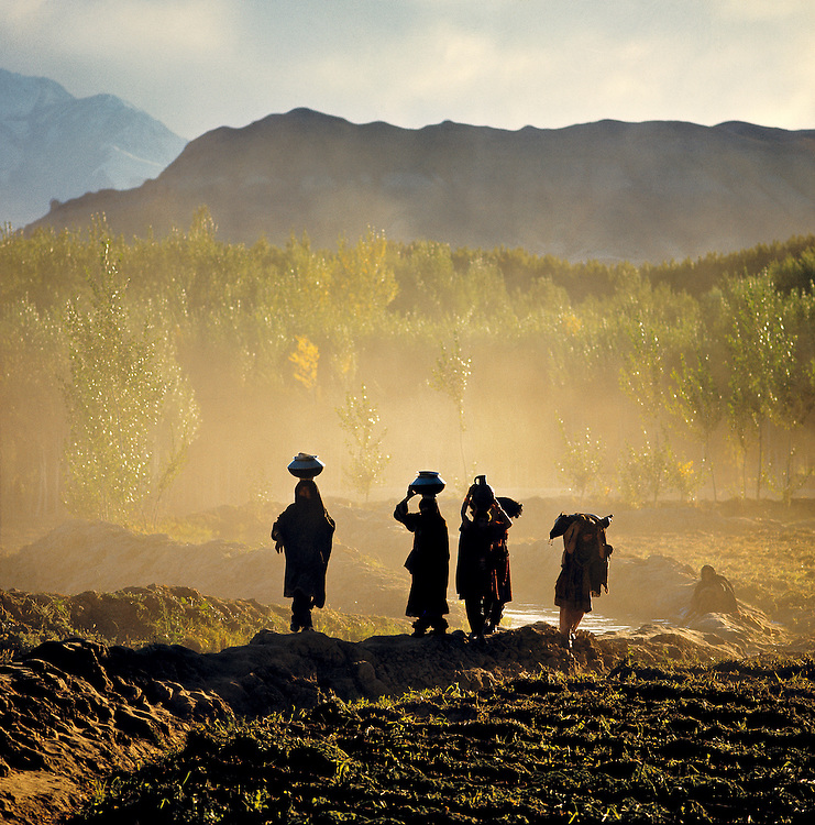Silhouetted women balance water jugs on their heads as they walk homeward in the Bamian Valley of Afghanistan.