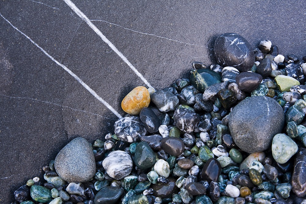 Colorful stones with quartz lines on the beach at Shi Shi Beach, Olympic National Park, Washington.