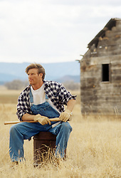 rugged rancher seated in a field holding an ax