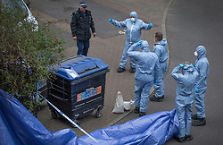 © Licensed to London News Pictures. 08/04/2016. London, UK.  Police forensics officers prepare to place a tent arround some rubbish bins in front of  Block E on the Peabody estate where local residents claim the body of missing policeman Gordon Semple was found. A man was arrested yesterday. Photo credit: Peter Macdiarmid/LNP