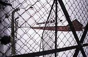 Der Sicherheitszaun im ehemaligen Konzentrationslager Auschwitz Birkenau am Tag der Gedenkfeiern zur 60. Jährigen Befreiung des Konzentrationslagers durch die Rote Armee am 27. Januar 1945. Im Hintergrund Baracken in welchen die Häftlinge untergebracht waren.
