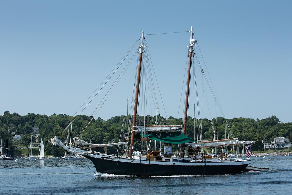 Camden, ME - 11 August 2014. The windjammer schooner Mistress motoring out of Camden with tourists on deck.
