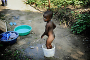 Chlid bathing in Lunsar, Sierra Leone.