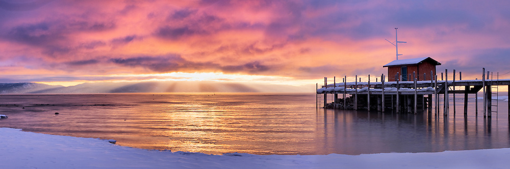 An image of  sunrise on Lake Tahoe and Commons Beach pier.  Pink and orange alpenglow clouds and beams of light arecoming through the clouds