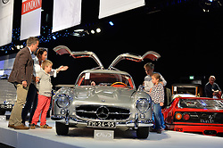 © Licensed to London News Pictures. 08/09/2013. London, England. RM Auctions Classic Car auction at Battersea Evolution, London. Photo credit : Mike King/LNP. RM Auctions 8-9 September 2013 at Battersea Evolution. A family look at a 1956 Mercedes Benz 300 SL gullwing.