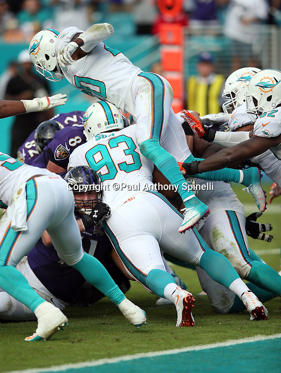 Miami Dolphins defensive tackle Ndamukong Suh (93) pushes the pile backwards while Miami Dolphins strong safety Reshad Jones (20) dives over the top of a pile of players on a fourth down goal line stand by the Dolphins that stops a run attempt by Baltimore Ravens quarterback Matt Schaub (8) and turns the ball over to the Dolphins on downs during the 2015 week 13 regular season NFL football game against the Baltimore Ravens on Sunday, Dec. 6, 2015 in Miami Gardens, Fla. The Dolphins won the game 15-13. (©Paul Anthony Spinelli)
