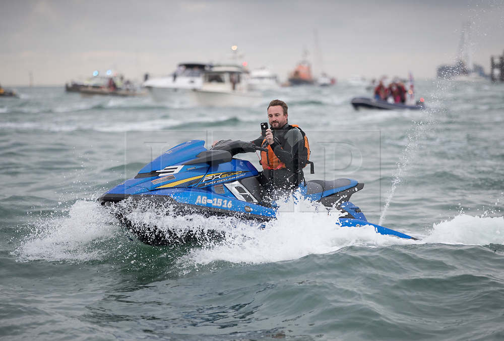 © Licensed to London News Pictures. 16/08/2017. Portsmouth, UK. A man takes a phone photograph from a jet ski as a flotilla of small boats follows the Royal Navy's new aircraft carrier HMS Queen Elizabeth as she enters her home port of Portsmouth for the first time. The new ship at 65,000 tonnes is the biggest warship ever built in the UK. Photo credit: Peter Macdiarmid/LNP