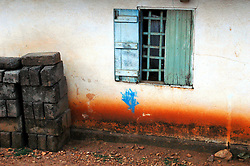 Ghana, Adaklu, Titikope, 2007. Heavy seasonal rains spatter Southern Ghana's red earth on house walls.