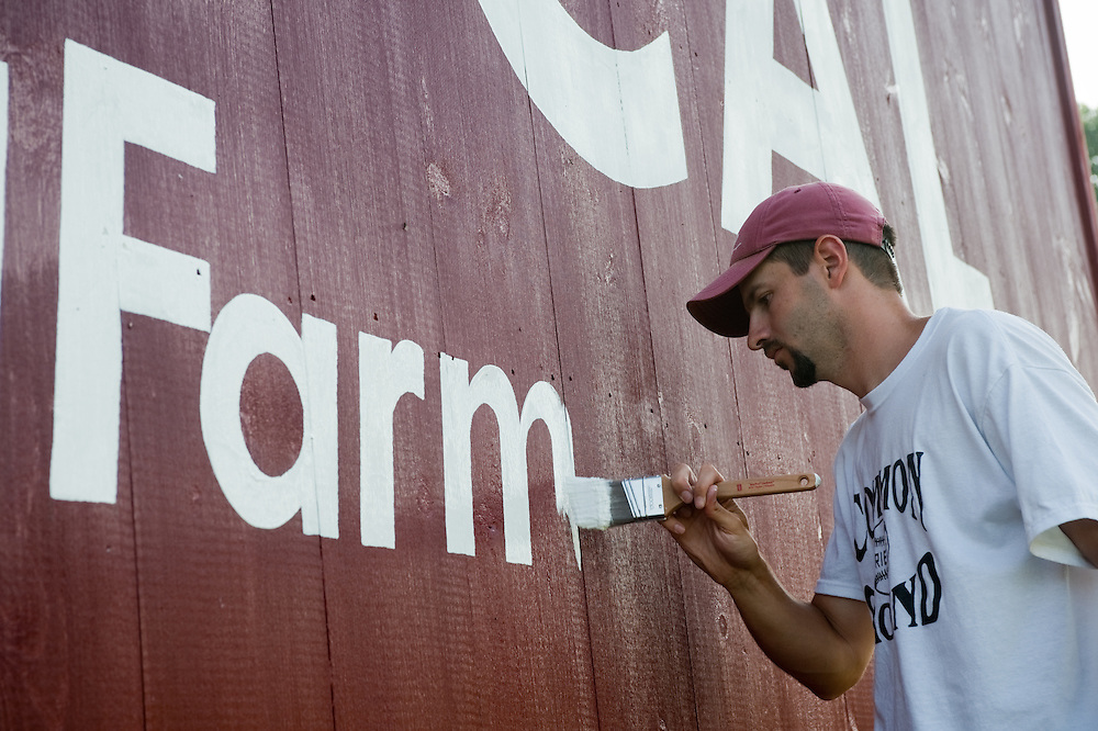 Man painting the side of a barn