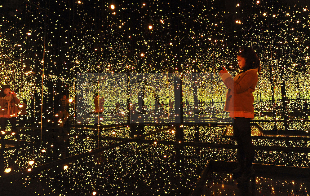 © Licensed to London News Pictures. 07/02/2012, London, UK. A woman takes a picture of 'Infinity Mirrored Room - Filled With The Brilliance of Life 2011. This is Kusama's largest mirrored room to date. Press preview of Yayoi Kusama at the Tate Gallery Bankside today 7th February 2012. The exhibition spans six decades of the artists work. Kusama is one of Japan's best known living artists.  Photo credit : Stephen Simpson/LNP