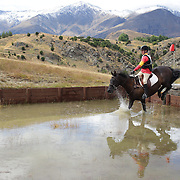 Lee Warren riding Painted Black in action at the water jump during the Cross Country event at the Wakatipu One Day Horse Trials at the Pony Club grounds,  Queenstown, Otago, New Zealand. 15th January 2012. Photo Tim Clayton