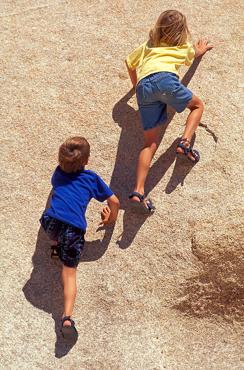 Kids climbing on granite boulder, Joshua Tree National Park, California USA