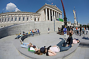 Ringstrasse. The Parlament (Parliament). High school kids relaxing at the fountain.