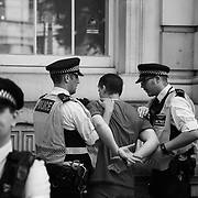 A man is detained by police outside Downing Street June 21st 2017, London, United Kingdom. He was alledgedly not part of the demonstration and was antagonising the crowd for no reason. Hundreds marched protesting against the Government's respond to the Grenfell Tower disaster. The mood was angry but peacefull and ended on Parliament Square green after police made people get of the streets and let traffic re-assume.