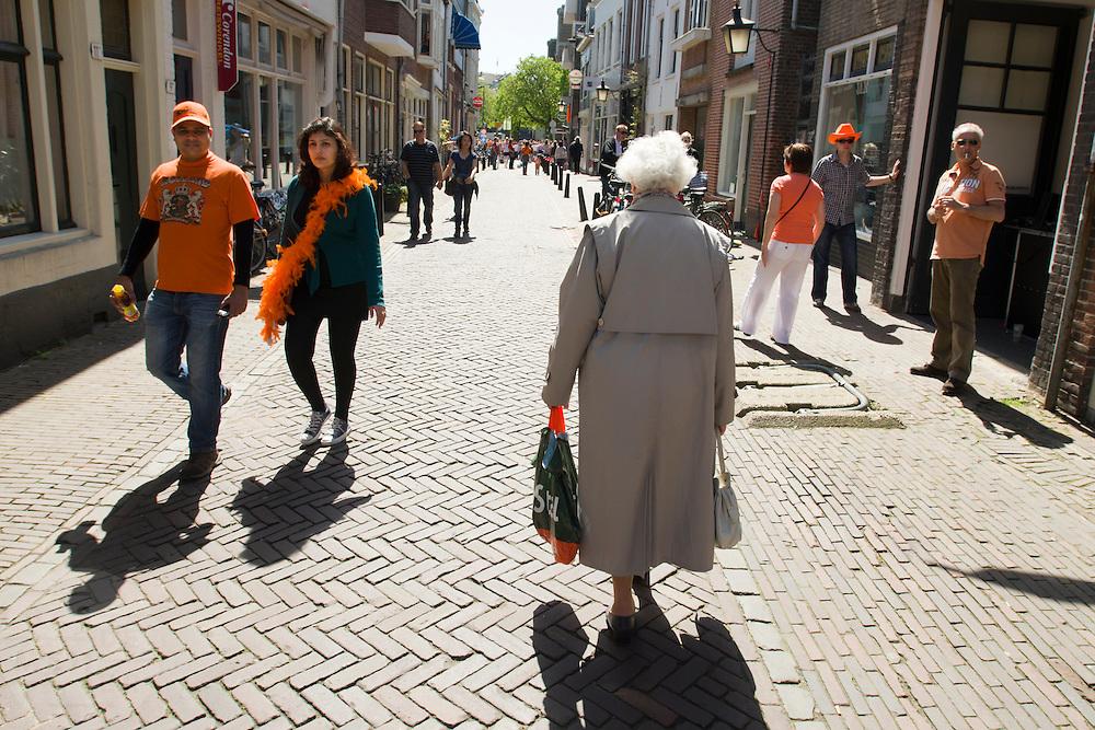 Een oudere vrouw loopt met langs de feestvierders tijdens Koninginnedag in Utrecht.<br /> <br /> An elder woman is passing partygoers at Queensday in Utrecht.