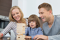 Happy parents and son playing with wooden blocks at home