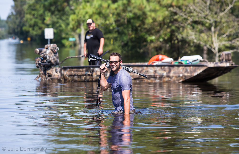 Sept 1, 2017  volenteer helping evacute people checking  in Vidor, Texas where floodwater continued to rise days after Hurricane Harvey first made landful holds up his gun which fell into the water and had to be retrieved.