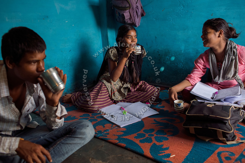 While having an afternoon chai tea, Poonam, 13, (right) is reviewing school homework with her older sister Jyoti, 14, sitting with their older brother Ravi, 15, on the floor of their newly built home in Oriya Basti, one of the water-contaminated colonies in Bhopal, Madhya Pradesh, India, near the abandoned Union Carbide (now DOW Chemical) industrial complex.