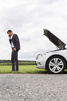 Side view of young businessman using cell phone by broken car at countryside