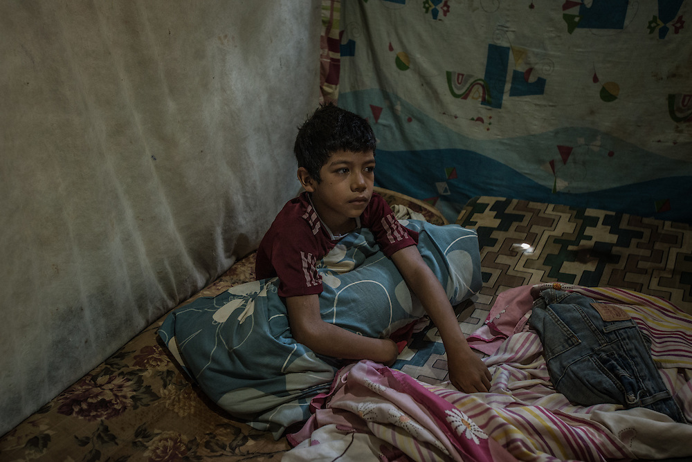 EL DIQUE, VENEZUELA - MAY 24, 2016: Omar Márquez, 8, rests in bed while sick with malaria in his home, constructed of adobe and tree branches. Omar's mother has been going to the malaria clinic regularly to try to find medicine for Omar and his brother, who is also currently sick with malaria, but has not been able to find it yet.  Doctors keep telling her to come back the next day.  10 people in Omar's family have contracted malaria, his grandfather died on May 3rd after contracting a fatal strain.  Their family lives next to a stagnant creek where malaria-carrying mosquitos thrive.  Their home does not have running water, so they keep several buckets around their home to catch rain water.  All the standing water attracts mosquitos. The townspeople in El Dique are gathering money to spray their own walls with pesticide to kill mosquitos for the first time. Doctors say they are only one of countless locations where government fumigators no longer arrive.  PHOTO: Meridith Kohut for The New York Times