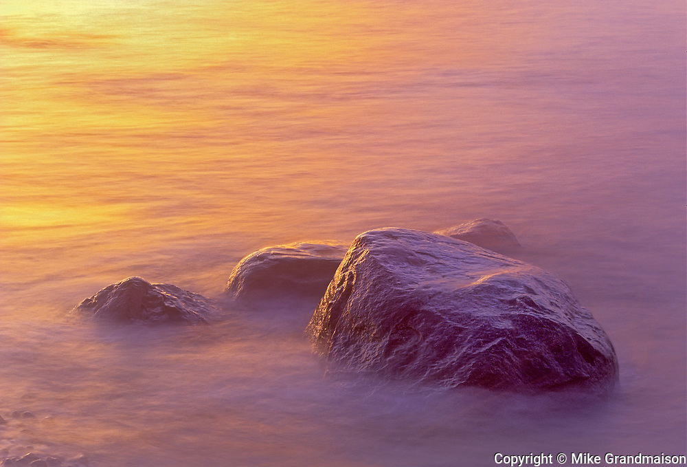 Waves of Lake Winnipeg crashing on shoreline rocks at sunrise<br /> Hecla Provincial Park<br /> Manitoba<br /> Canada