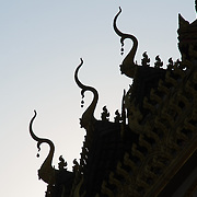 The intricate patterns that form the decorations on the roof of a Wat (Buddhist temple) are silhoutted against a clear sky. Vientiane, Laos.