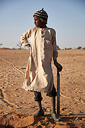 Adam Alouso, 13 years old dig holes in the sand for a shelter at a camp of displaced people in the neighbourhood of Chateau, Diffa, Niger on February 12, 2016. They come from a village in Bosso commune, Nigeria and arrived with their parents by foot which took 8 days. The camp is mixed between displaced people from Niger, Nigeria and Chad. They have fled attacks by the militant group Boko Haram on their villages and it's ongoing conflicts with the armies of each country. Caritas undertook a distribution of mosquito nets, cooking pots, sleeping covers, hygiene kits, clothes and cash transfers to the displaced. 228 households received support from Caritas among an estimated 1500 households in the  vicinity of Chateau. There is still great need. There is no school system in place for the children and the housing is not adequate for many as more people arrive each day escaping hostilities. <br /> <br />  'We were scared of being attacked so left. The majority of the village left because we were scared Boko Haram would come in the night and take us away.'