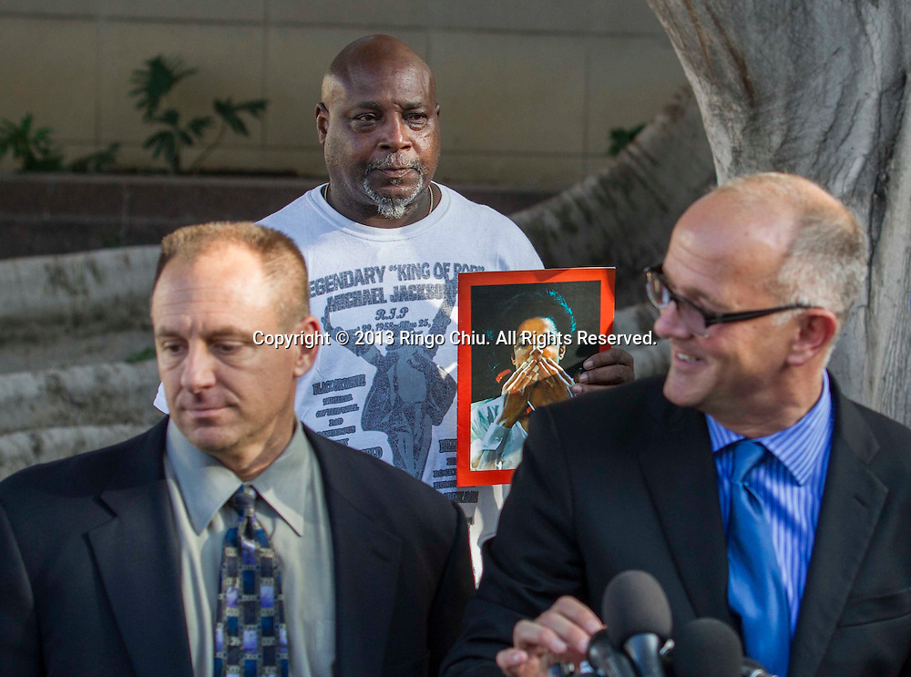 10月2日,在美国加利福尼亚州洛杉矶市高级法院外,当AEG总法律顾问会见记者时,一名支持者展示持迈克尔杰克逊的相片。当日,对于杰克逊家族提起的迈克尔杰克逊非正常死亡诉讼,陪审团一致裁定杰克逊家族败诉,AEG公司胜诉。(新华社发 赵汉荣摄)<br /> A supporter shows a picture of Michael Jackson as AEG Live lead attorney Marvin Putnam, right and Shawn Trell, left, general counsel for AEG Live, talk to reporters outside a courthouse on Wednesday, October 2, 2013, in Los Angeles, California.  A jury cleared AEG Live of negligence in a case that attempted to link the death of Michael Jackson to the company that promoted his ill-fated comeback shows.(Photo by Ringo Chiu/PHOTOFORMULA.com)