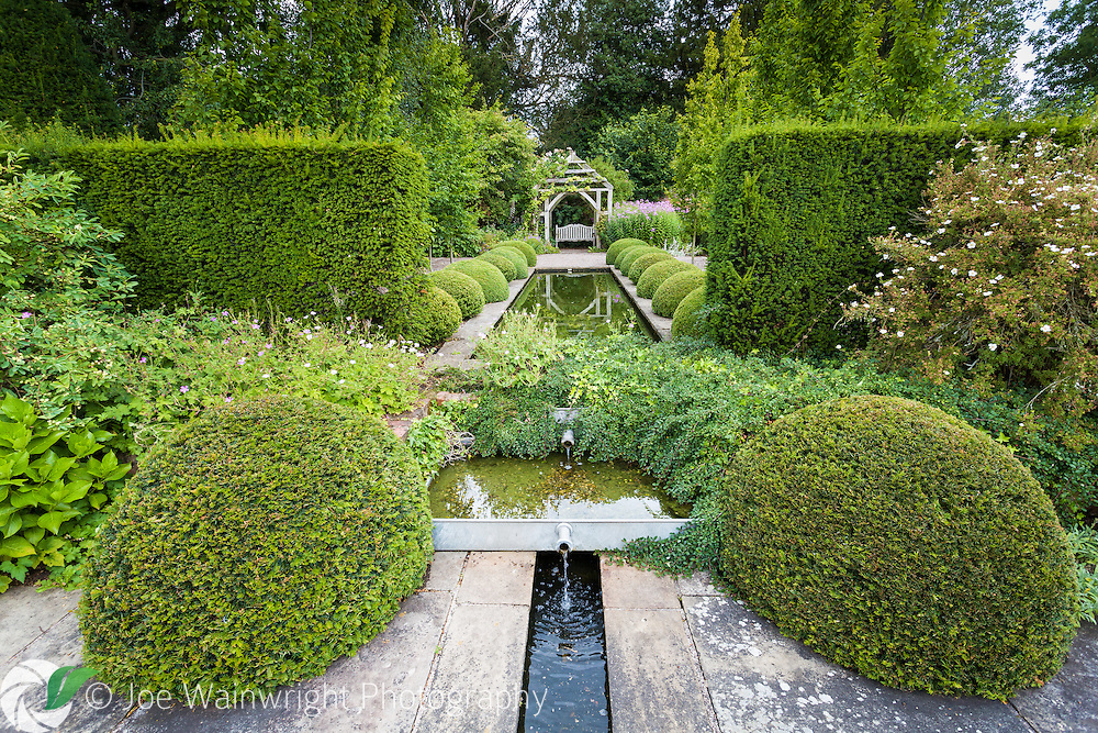 The symmetrical Rill Garden, features a wide upper and narrow lower rill, York Stone paving and two rows of Buxus sempervirens balls.