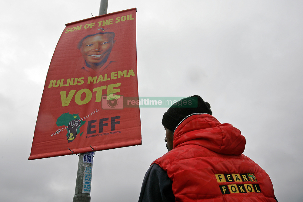 Wednesday 8th May 2019.<br /> Sinenjongo High School, Joe Slovo Park,<br /> Milnerton, Cape Town, <br /> Western Cape, <br /> South Africa.<br /> <br /> SOUTH AFRICAN GENERAL ELECTIONS 2019!<br /> <br /> SOUTH AFRICAN PROVINCIAL AND NATIONAL ELECTIONS 2019! <br /> <br /> EFF (Economic Freedom Fighters) political party supporter Lungelo Eric Zimasa Mankato (38) stands next to and under a EFF political party banner as he wears his political party's bright red puffy half jacket with the words 'Fear Fokol' (Fear Fuck All) on the back of his jacket after casting his obvious vote at Sinenjongo High School, Joe Slovo Park near Milnerton, Cape Town, Western Cape, South Africa.  <br /> <br /> Registered South African Voters head to the various IEC (Independent Electoral Commission) Voting Stations where they are registered to vote as they cast their votes and take part in voting and other activities on Voting Day 8th May 2019 during the South African General Elections 2019. Voters from across the nation stood in queue's along with many others to vote in the Provincial and National Elections being held in South Africa on Wednesday 8th May 2019.   <br />  <br /> Copyright © Mark Wessels. All Rights Reserved. No Usage Without Permission.<br /> <br /> PICTURE: MARK WESSELS. 08/05/2019.<br /> +27 (0)61 547 2729.<br /> mark@sevenbang.com<br /> studioseven@mweb.co.za<br /> www.markwesselsphoto.com