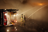 JEROME A. POLLOS/Press..Firefighter keep a steady stream of water on the backside of the 7-11 convenience store. So much water was used in fighting the blaze that the area of 5th Street near the fire had accumulated nearly a foot of standing water.