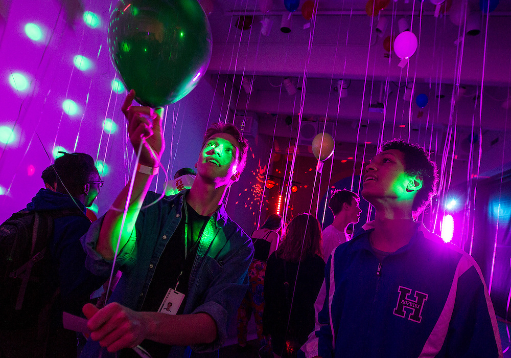 Partygoers reach for balloons with questions attached during a mingling game at Youth Night at the Walker Art Center in Minneapolis October 23, 2015.
