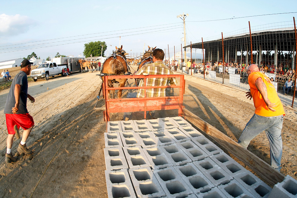 """Charlie Beeman, left, and Bud Lowe, right, chase Roger Beeman, center, as one of their horse teams pulls a sledge weighted with 50-pound cinder blocks during the horse pulling competition at the Mercer County Fair in Aledo, IL on Thursday, July 14.  The trio came from over 700 miles away in Nashville, Michigan to compete.  """"It's in my blood,"""" says Charlie, whose father pulled horses as well.  The Beeman brothers and Bud ended up winning the competition by pulling over 13,500 pounds."""