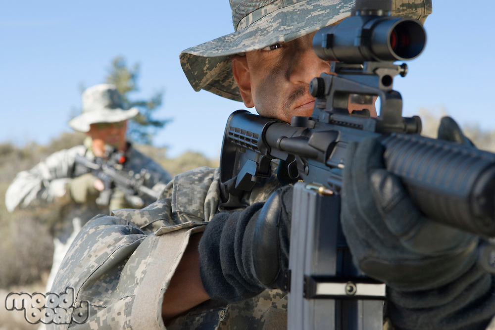 Soldiers aiming rifles in field, focus on soldier in foreground