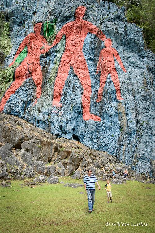 Man and Son walk in front of Mural de la Prehistoria painted by Leonvglido Gonzalez Morillo