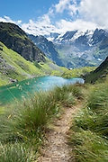 The Grand Combin Massif rises above Lake Louvie in the Pennine/Valais Alps, Switzerland, Europe.  Optionally stay overnight in dorms at Cabane de Louvie. The dramatic Chamois Path (Sentier des Chamois) starts at La Chaux ski lift and ends at Fionnay PostBus. Cross Col Termin (2648m/8688 ft) in Haut Val de Bagnes nature reserve and descend to Lake Louvie via 1800s stone barns to the north, then to Fionnay (640 m up, 1415 m down in 8.5 hours).