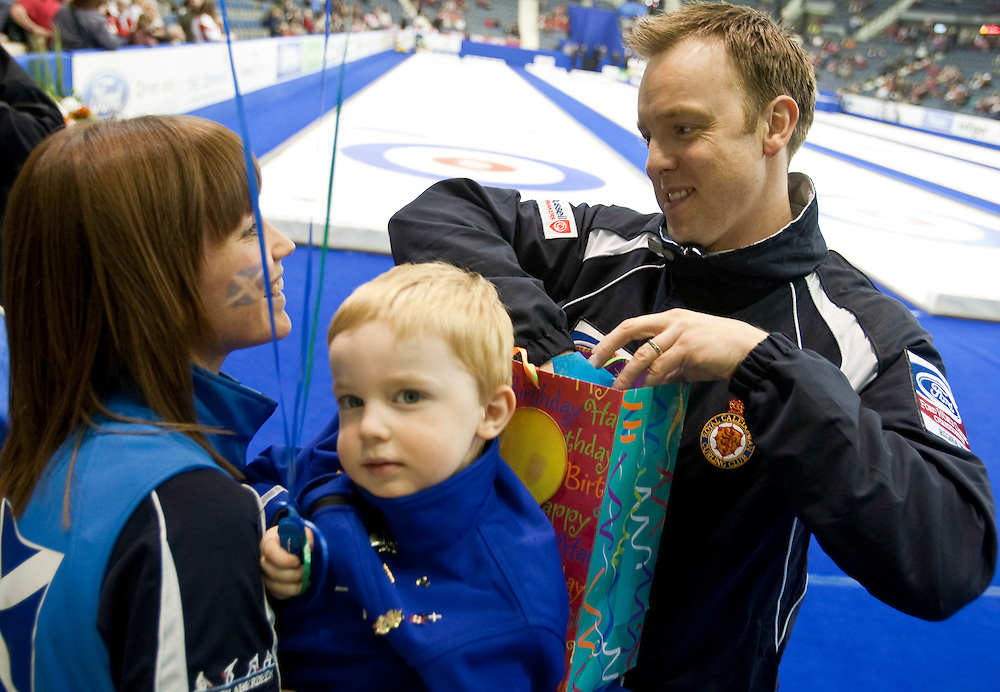 Scotland's skip Tom Brewster receives a birthday gift from his wife Kim and his son Ethan before his gold medal game against Canada at the Ford World Men's Curling Championships in Regina, Saskatchewan, April 10, 2011.<br /> AFP PHOTO/Geoff Robins