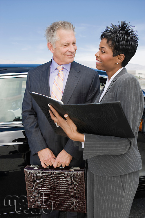 Senior businessman with mid-adult businesswoman standing in front of car.