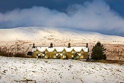 © Licensed to London News Pictures. 28/01/2020. Ribblehead UK. A row of snow covered houses near Ribblehead in the shadow of Whernside mountain in the Yorkshire Dales this morning. Photo credit: Andrew McCaren/LNP