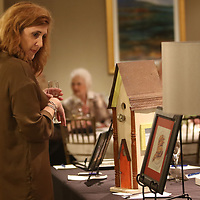 Kristi Lake looks through the many items up for auction Saturday at the Gum Tree Museum of Art's For the Love of Art Gala at the Tupelo Country Club