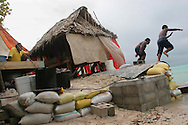 A family living next to the sea, on the South Pacific island of Kiribati, re-enforce their property with a sea wall made of sand bags to stop the encroaching sea from eroding their land.