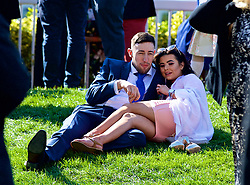 LIVERPOOL, ENGLAND - Thursday, April 6, 2017: A couple relax on a grass embankment, during The Opening Day on Day One of the Aintree Grand National Festival 2017 at Aintree Racecourse. (Pic by David Rawcliffe/Propaganda)
