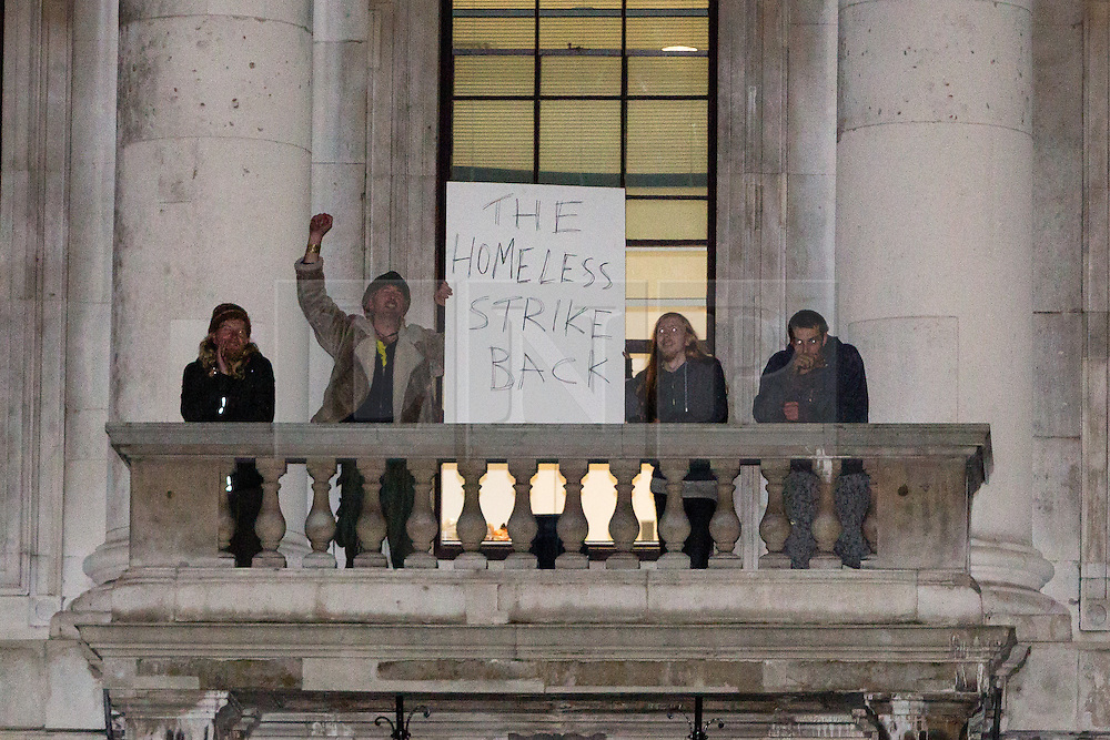 """© Licensed to London News Pictures. 29/12/2015. London, UK. Squatters hold a sign with """"The homeless strike back"""" from a balcony of the Royal Mint building. Squatters have occupied the Royal Mint building, located opposite the Tower of London on the border of the City of London to protest against homelessness and highlight how empty buildings could provide shelter for rough sleepers. The site was previously used to manufacture British coins but is currently vacant and activists argue that this along with other vacant commercial buildings could be used to provide short term shelter for the homeless. Photo credit : Vickie Flores/LNP"""