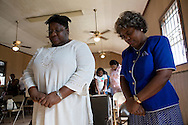 Sunday services at the Greater Little Zion Baptist Church located in the Lower 9th Ward of New Orleans. Local area residents attend religious services in the hot semi-restored Church. There is no air conditioning and it is very warm inside on a hot August day. The Church is still in need of major repair due to flooding by  Hurricane Katrina.