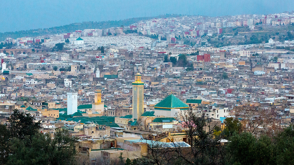 FEZ, MOROCCO - 1ST FEBRUARY 2018 - View over the old Fez Medina, with the Al-Karaouine Mosque and University (building on the left with green tiled roof and white Minaret) and the Zawiya Moulay Idriss II (larger building on the right with pyramid roof).<br />