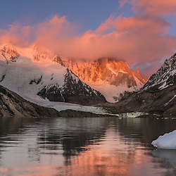 Some clouds surround Mount Fitzroy at sunset while the granite rocks color red and purple, Parque Nacional los Glaciers, Argentina.