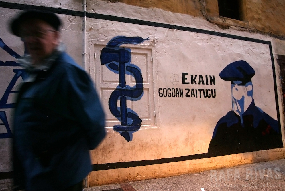 "A man walks past a mural painting representing the pro-independence armed Basque group ETA logo and honouring an activist who died when the bomb that he was going to plant exploded and killed him and other two ETA members. Text reads in Basque ""Ekain (name of the member) we remember you"", 23 March 2006 in the northern Spanish Basque town of Hernani. PHOTO RAFA RIVAS"